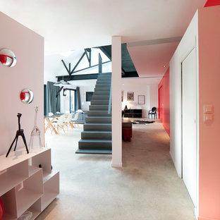 Idées déco pour un couloir contemporain de taille moyenne avec un mur rouge et béton au sol.