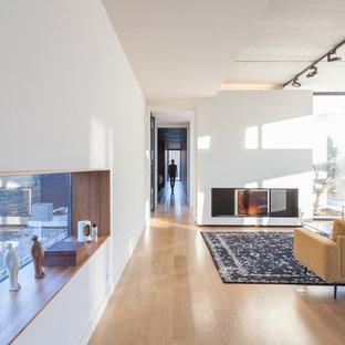 Aménagement d'un grand couloir contemporain avec un mur blanc et un sol en bois clair.
