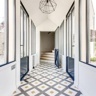 Cette image montre un couloir design avec un mur blanc et un sol multicolore.