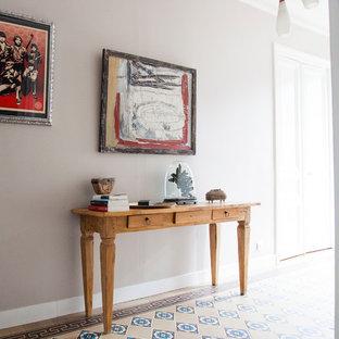 Idée de décoration pour un couloir design de taille moyenne avec un mur beige et un sol en carrelage de céramique.