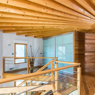 Exemple d'un couloir tendance avec un mur blanc, un sol en bois brun et un sol marron.