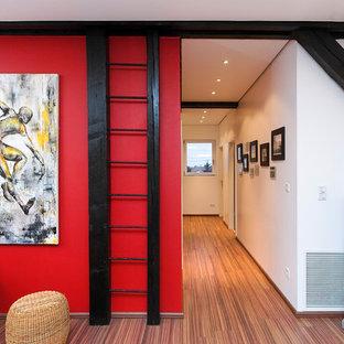 Idées déco pour un couloir contemporain de taille moyenne avec un mur rouge, un sol en bois brun et un sol marron.
