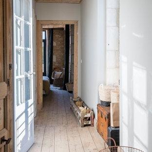 Idée de décoration pour un couloir méditerranéen avec un mur blanc, un sol en bois clair et un sol beige.