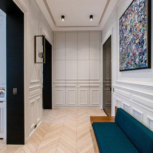 Idées déco pour un couloir contemporain avec un sol en bois clair et un sol beige.