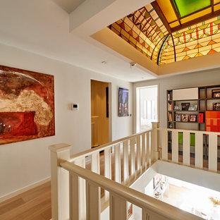 Cette photo montre un couloir tendance avec un mur gris, un sol en bois clair et un sol beige.