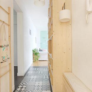 Inspiration pour un couloir nordique de taille moyenne avec un mur blanc et un sol en carrelage de céramique.