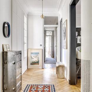 パリのエクレクティックスタイルのおしゃれな廊下 (白い壁、淡色無垢フローリング、ベージュの床) の写真