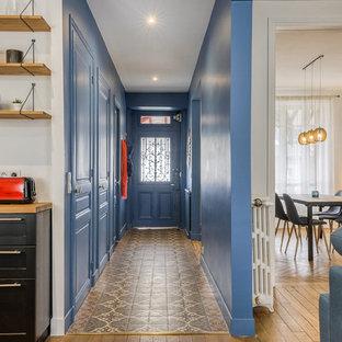 パリの広い北欧スタイルのおしゃれな廊下 (青い壁、テラコッタタイルの床) の写真