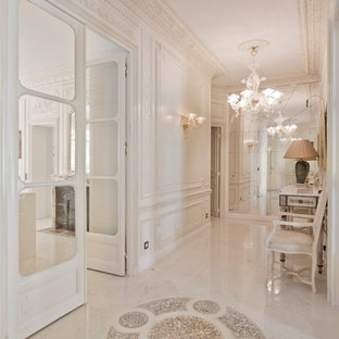 Idée de décoration pour un grand couloir tradition avec un mur beige et un sol en marbre.