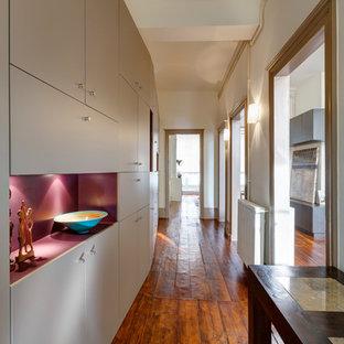 Modern inredning av en mellanstor hall, med beige väggar och mellanmörkt trägolv