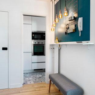 Cette photo montre un couloir scandinave avec un mur blanc, un sol en bois clair et un sol marron.