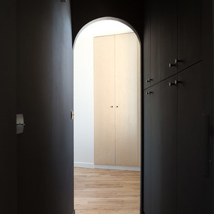 Esempio di un ingresso o corridoio tropicale di medie dimensioni con pareti nere e parquet chiaro