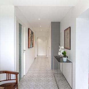 Cette image montre un couloir design avec un mur blanc et un sol gris.