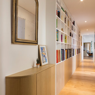 Exempel på en stor modern hall, med vita väggar, ljust trägolv och beiget golv