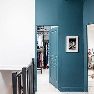 Esempio di un ingresso o corridoio moderno con pareti blu e pavimento in legno verniciato
