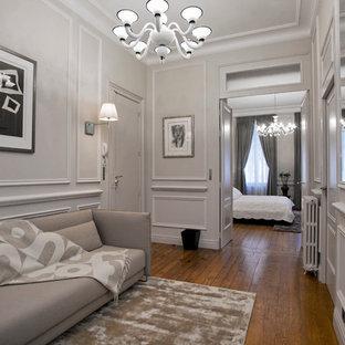 Réalisation d'un couloir design de taille moyenne avec un mur gris et un sol en bois brun.