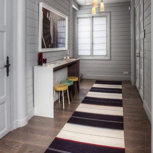 Aménagement d'un grand couloir bord de mer avec un mur gris et un sol en bois brun.