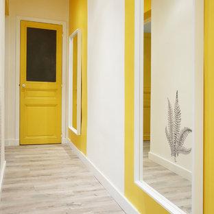 Idées déco pour un couloir scandinave avec un mur jaune et un sol en bois brun.