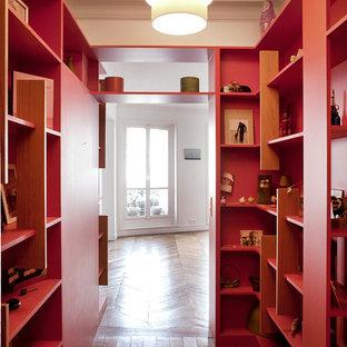 Cette photo montre un couloir tendance de taille moyenne avec un mur rouge et un sol en bois brun.