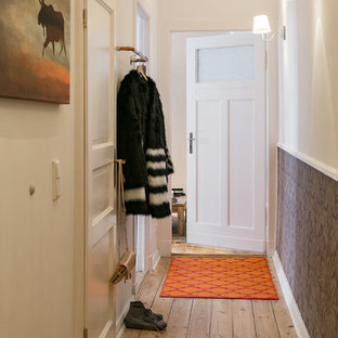 Photo of a mid-sized traditional hallway in Berlin with white walls, medium hardwood floors and brown floor.