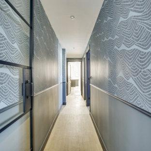 Exempel på en stor modern hall, med blå väggar, ljust trägolv och beiget golv