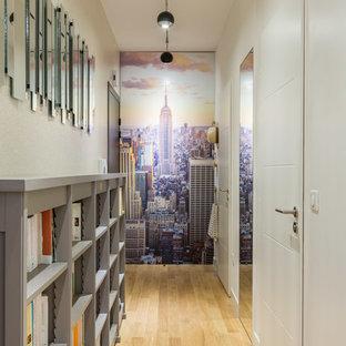 Inspiration pour un couloir design de taille moyenne avec un mur blanc et un sol en bois clair.