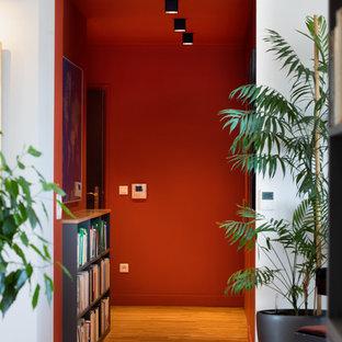 Aménagement d'un couloir moderne avec un mur orange et un sol en bois clair.
