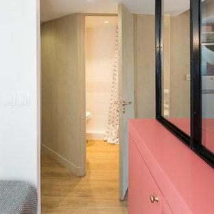 Inredning av en mellanstor hall, med rosa väggar, mellanmörkt trägolv och beiget golv