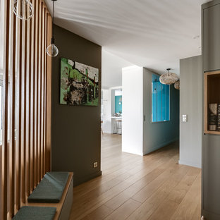 Idées déco pour un couloir contemporain avec un mur marron, un sol en bois brun et un sol marron.