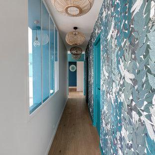 Cette photo montre un couloir tendance avec un mur bleu, un sol en bois clair et un sol marron.