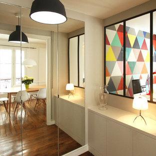 Idée de décoration pour un couloir design de taille moyenne avec un mur blanc et un sol en bois foncé.