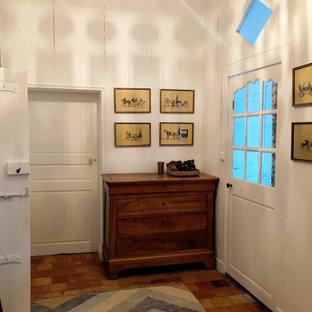 На фото: коридор среднего размера в стиле современная классика с белыми стенами, полом из терракотовой плитки и розовым полом