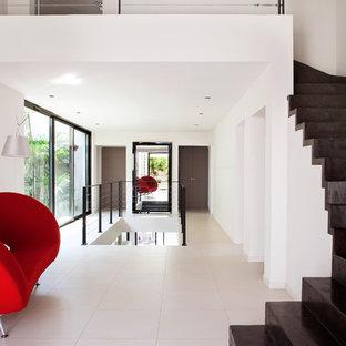 Cette image montre un grand couloir design avec un mur blanc et un sol blanc.