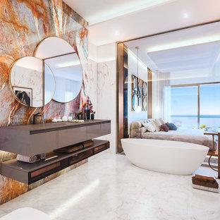 Inredning av ett modernt grå grått en-suite badrum, med ett fristående badkar, marmorkakel, marmorgolv, ett integrerad handfat, släta luckor, grå skåp, orange kakel, vit kakel och vitt golv