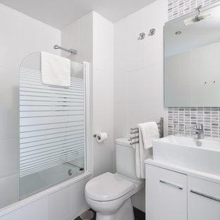 Imagen de cuarto de baño con ducha, contemporáneo, de tamaño medio, con armarios con paneles lisos, puertas de armario blancas, bañera empotrada, combinación de ducha y bañera, sanitario de dos piezas, baldosas y/o azulejos grises, baldosas y/o azulejos blancos, baldosas y/o azulejos de porcelana, paredes rojas y encimeras blancas