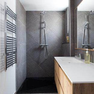 Ejemplo de cuarto de baño contemporáneo con armarios con paneles lisos, puertas de armario de madera clara, ducha a ras de suelo, baldosas y/o azulejos grises, paredes blancas, lavabo integrado, suelo gris, ducha abierta y encimeras blancas