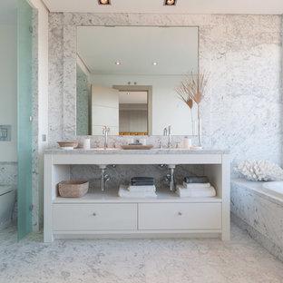 Foto de cuarto de baño principal, costero, grande, con armarios con paneles lisos, puertas de armario blancas, bañera empotrada y lavabo integrado