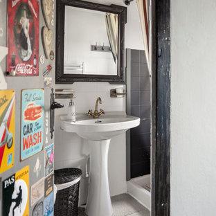 Imagen de cuarto de baño con ducha, bohemio, de tamaño medio, con baldosas y/o azulejos negros, baldosas y/o azulejos de cerámica, paredes blancas, suelo de baldosas de porcelana, ducha con cortina, encimeras blancas, lavabo con pedestal y suelo gris