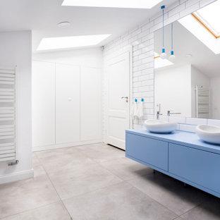 Diseño de cuarto de baño escandinavo con armarios con paneles lisos, puertas de armario azules, baldosas y/o azulejos blancos, baldosas y/o azulejos de cemento, paredes blancas, lavabo sobreencimera, suelo gris y encimeras azules