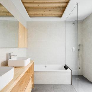 Foto de cuarto de baño minimalista con armarios abiertos, baldosas y/o azulejos grises, baldosas y/o azulejos beige, puertas de armario de madera clara, bañera encastrada, ducha a ras de suelo, baldosas y/o azulejos en mosaico, paredes blancas, lavabo sobreencimera, encimera de madera, suelo gris, ducha abierta y encimeras beige