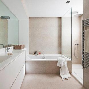 На фото: с высоким бюджетом большие главные ванные комнаты в скандинавском стиле с плоскими фасадами, белыми фасадами, ванной в нише, душем без бортиков, бежевой плиткой, каменной плиткой, бежевыми стенами, полом из известняка, монолитной раковиной и столешницей из искусственного кварца
