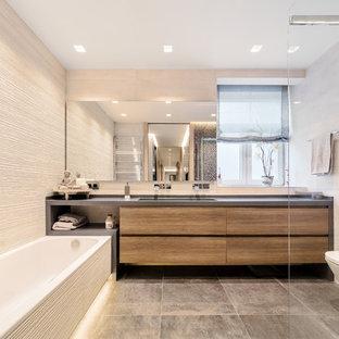Diseño de cuarto de baño principal, contemporáneo, de tamaño medio, con puertas de armario de madera en tonos medios, suelo gris, encimeras grises, armarios con paneles lisos, bañera encastrada, sanitario de una pieza, baldosas y/o azulejos beige y paredes beige