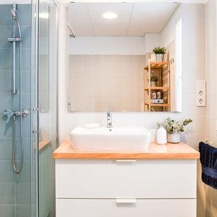 Ejemplo de cuarto de baño nórdico con armarios con paneles lisos, puertas de armario blancas, ducha empotrada, baldosas y/o azulejos azules, paredes blancas, lavabo sobreencimera, encimera de madera, suelo azul, ducha con puerta corredera y encimeras beige