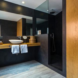 Foto di una stanza da bagno padronale design di medie dimensioni con ante lisce, ante in legno chiaro, doccia alcova, pareti nere, parquet chiaro, lavabo a bacinella, top in legno, doccia aperta e top marrone
