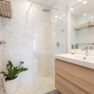 Foto de cuarto de baño con ducha, mediterráneo, de tamaño medio, con ducha a ras de suelo, paredes blancas, encimeras blancas, armarios con paneles lisos, puertas de armario de madera clara, baldosas y/o azulejos beige, suelo de baldosas tipo guijarro, lavabo integrado y ducha abierta