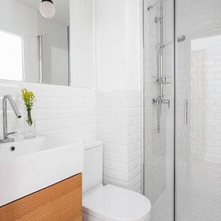 Foto de cuarto de baño con ducha, escandinavo, con armarios con paneles lisos, puertas de armario de madera oscura, sanitario de dos piezas, baldosas y/o azulejos blancos, baldosas y/o azulejos de cemento, paredes blancas y suelo multicolor