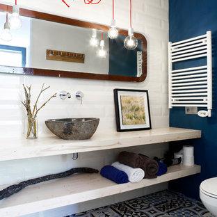 Ejemplo de cuarto de baño ecléctico con armarios abiertos, puertas de armario de madera clara, encimera de madera, baldosas y/o azulejos blancos, baldosas y/o azulejos de cemento, paredes azules, suelo de azulejos de cemento, lavabo sobreencimera, suelo multicolor y encimeras beige