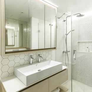 Modelo de cuarto de baño principal, actual, con armarios con paneles lisos, puertas de armario de madera clara, ducha a ras de suelo, baldosas y/o azulejos blancos, paredes blancas, lavabo sobreencimera, suelo gris, ducha con puerta con bisagras y encimeras blancas