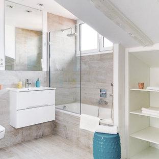 Imagen de cuarto de baño marinero con armarios con paneles lisos, puertas de armario blancas, bañera empotrada, combinación de ducha y bañera, sanitario de pared, baldosas y/o azulejos beige, paredes blancas, lavabo integrado, suelo beige, ducha abierta y encimeras blancas