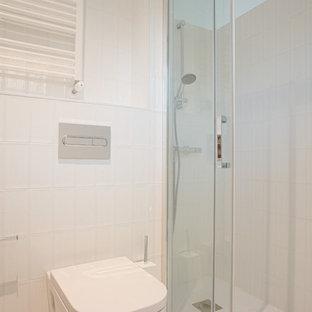 Стильный дизайн: главная ванная комната среднего размера в стиле лофт с открытыми фасадами, белыми фасадами, душем без бортиков, писсуаром, белой плиткой, керамической плиткой, белыми стенами, бетонным полом, настольной раковиной, столешницей из дерева, белым полом, душем с раздвижными дверями и коричневой столешницей - последний тренд